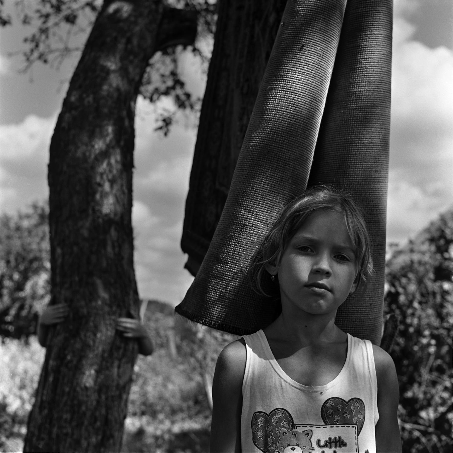 Black and white portrait photo of young girl standing before drying old carpet in backyard with a boy hiding behind tree
