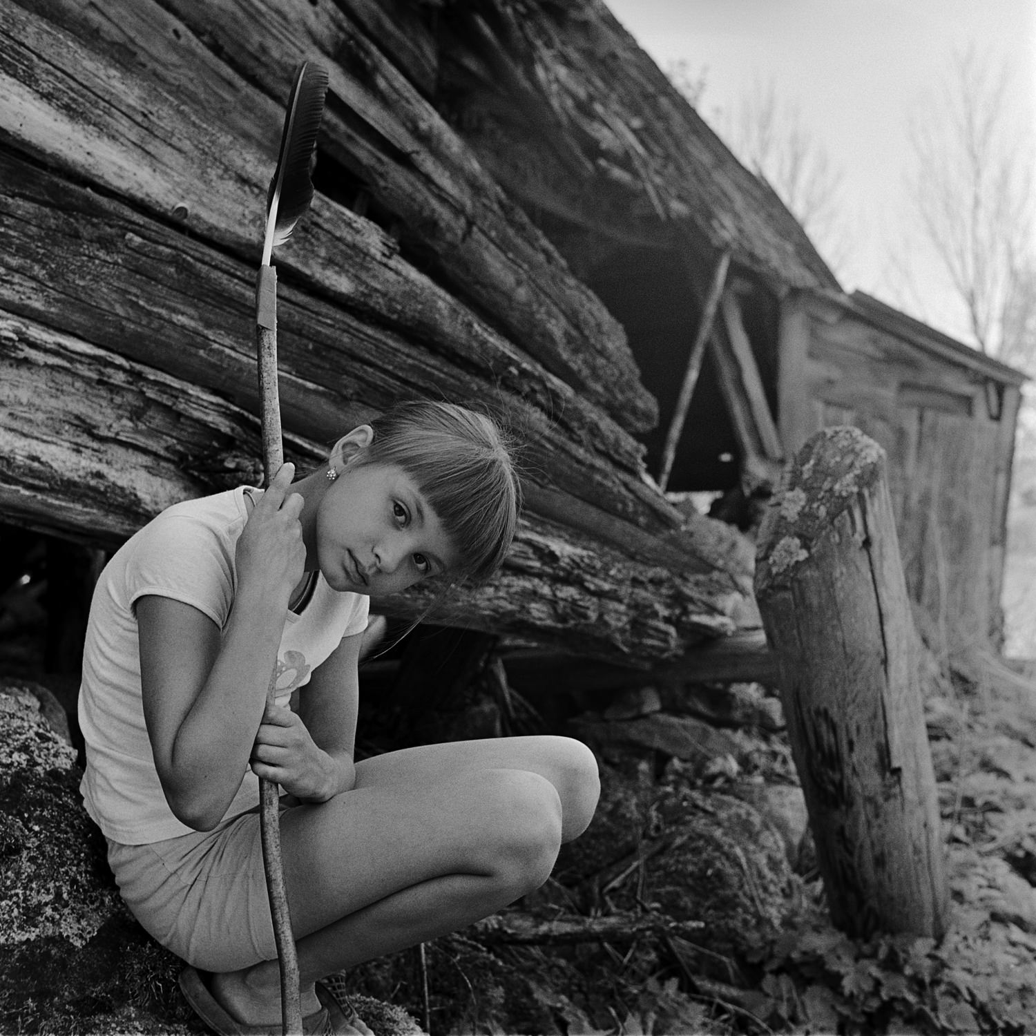 Documentary black-white portrait of young girl with a stick and feather in front of derelict country house in Belarus taken with medium format film camera