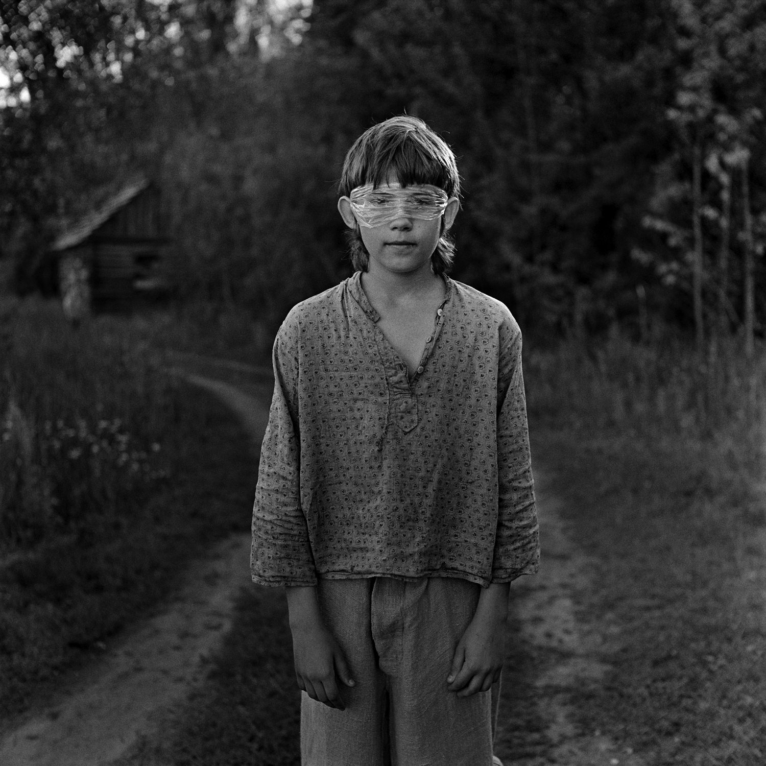 Medium format street portrait of young boy on the country road with old cotton t-shirt and plastic bag on his eyes taken on film