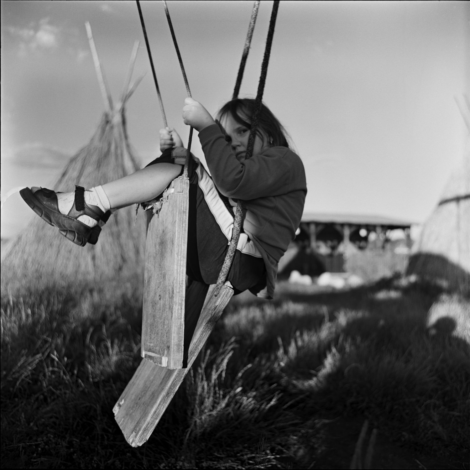 Black-and-white portrait photo of cute girl on broken swing with ropes in countryside rancho medium format film