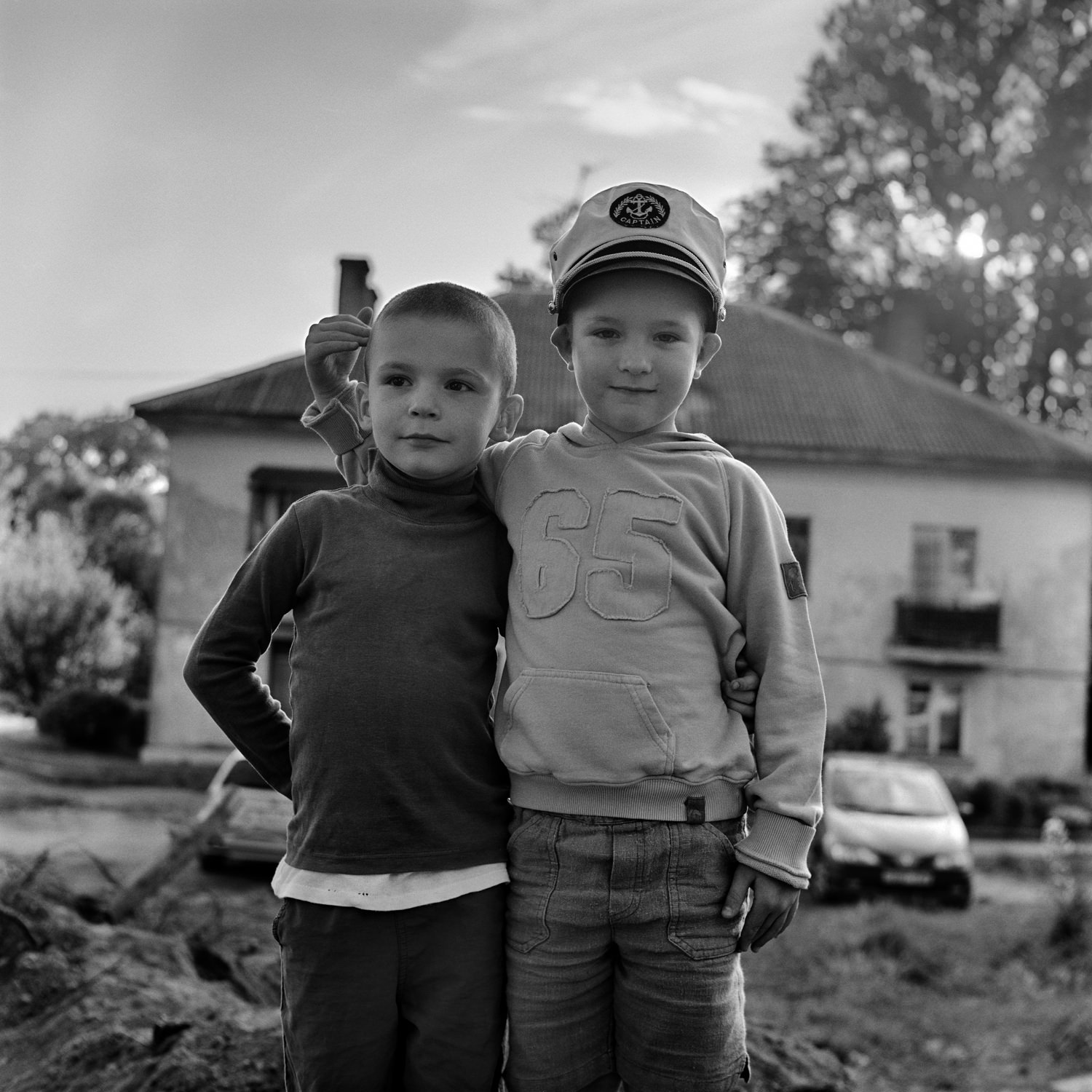 Documentary street portrait of two kid friends with derelict house taken on black white film