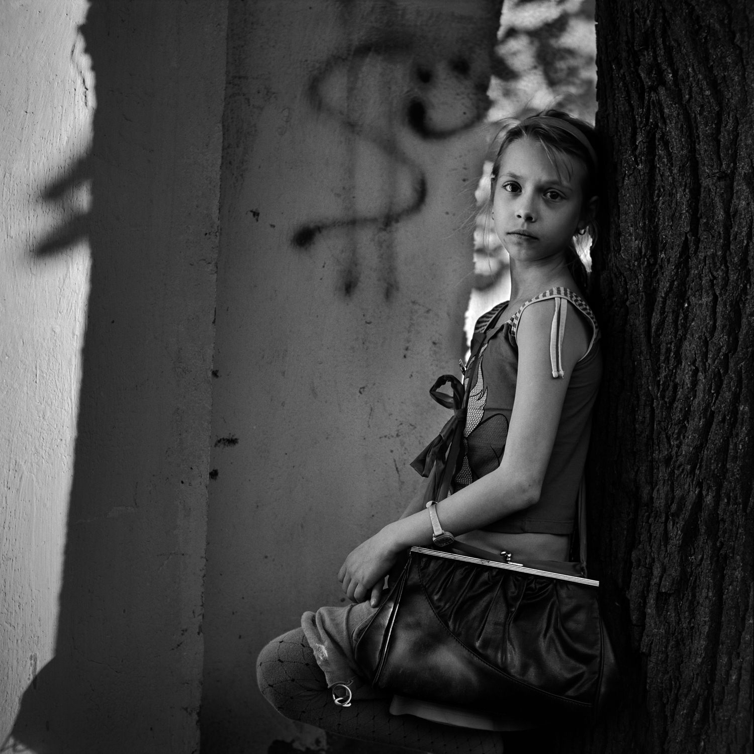 Emotional black white portrait photo of cute girl with old purse near big tree on