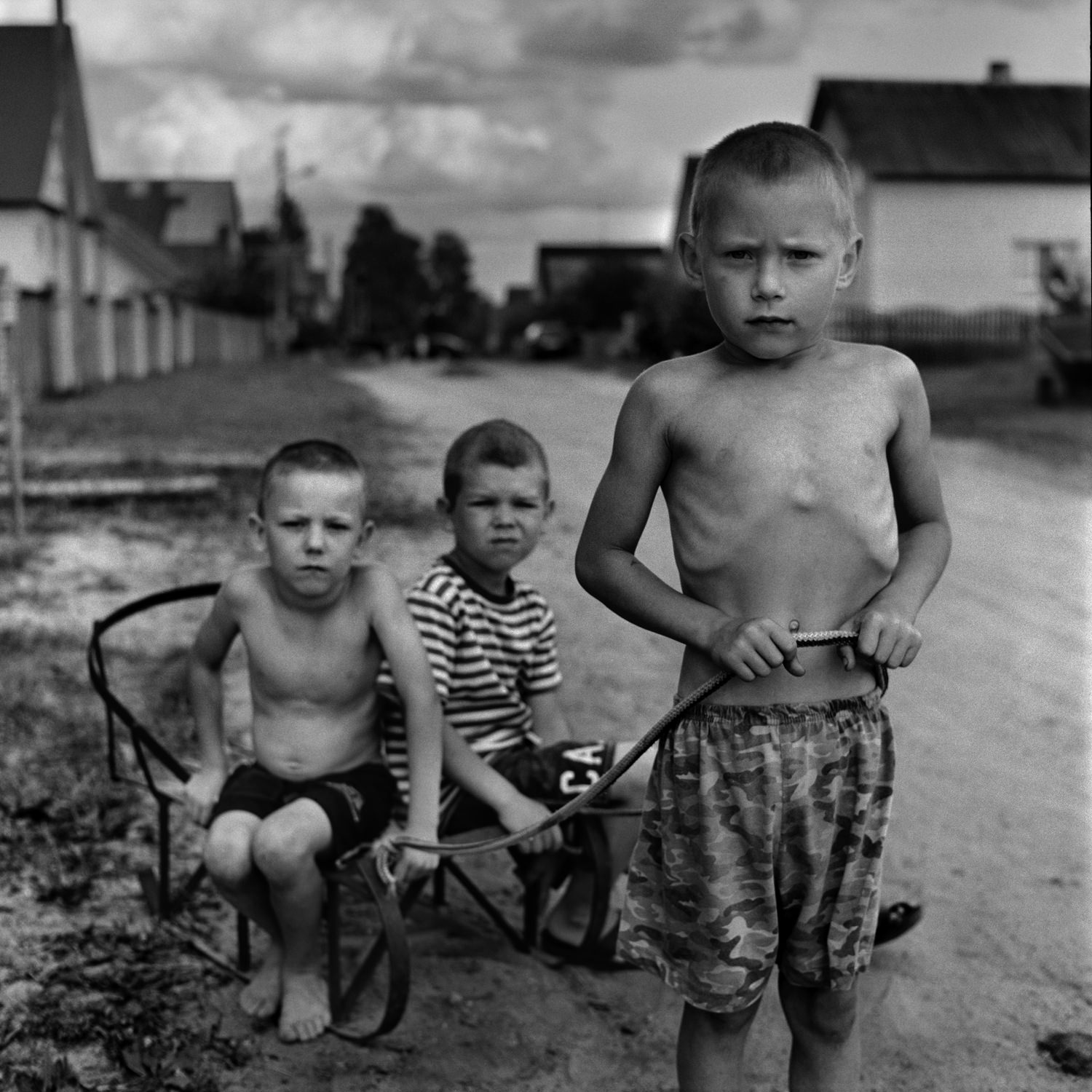 Documentary street portrait of three naked boys on countryside road with sled taken on Bronica SQ-Ai medium format camera and blac-and-white film