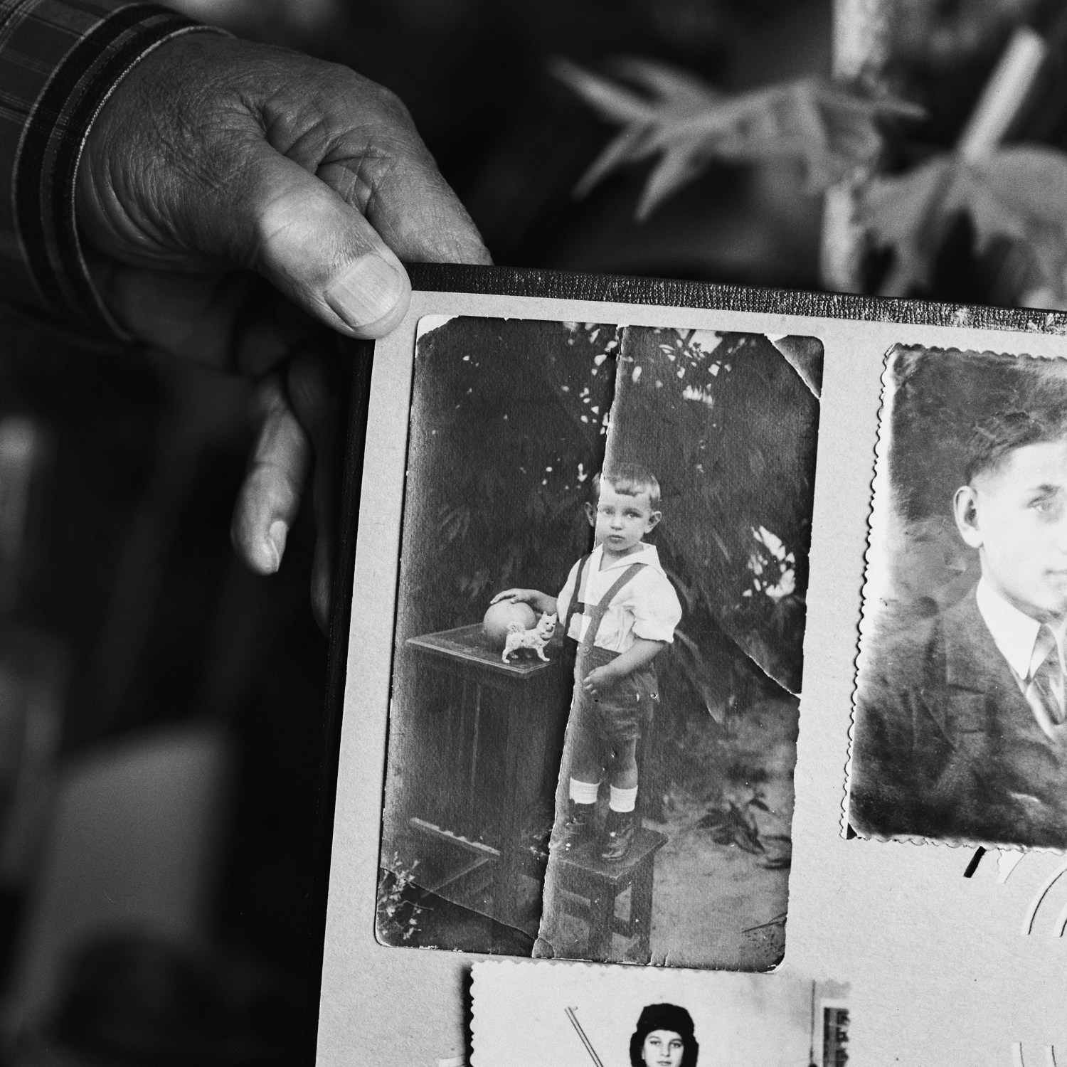 Veteran's hand showing his cracked childhood photos in memory album