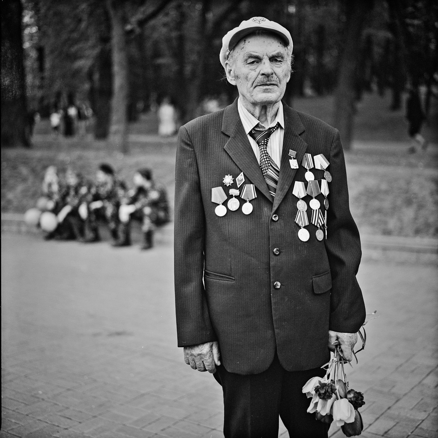 Documentary portrait of veteran of WW II with flowers in hand standed in Minsk park taken on black-and-white film and medium format camera