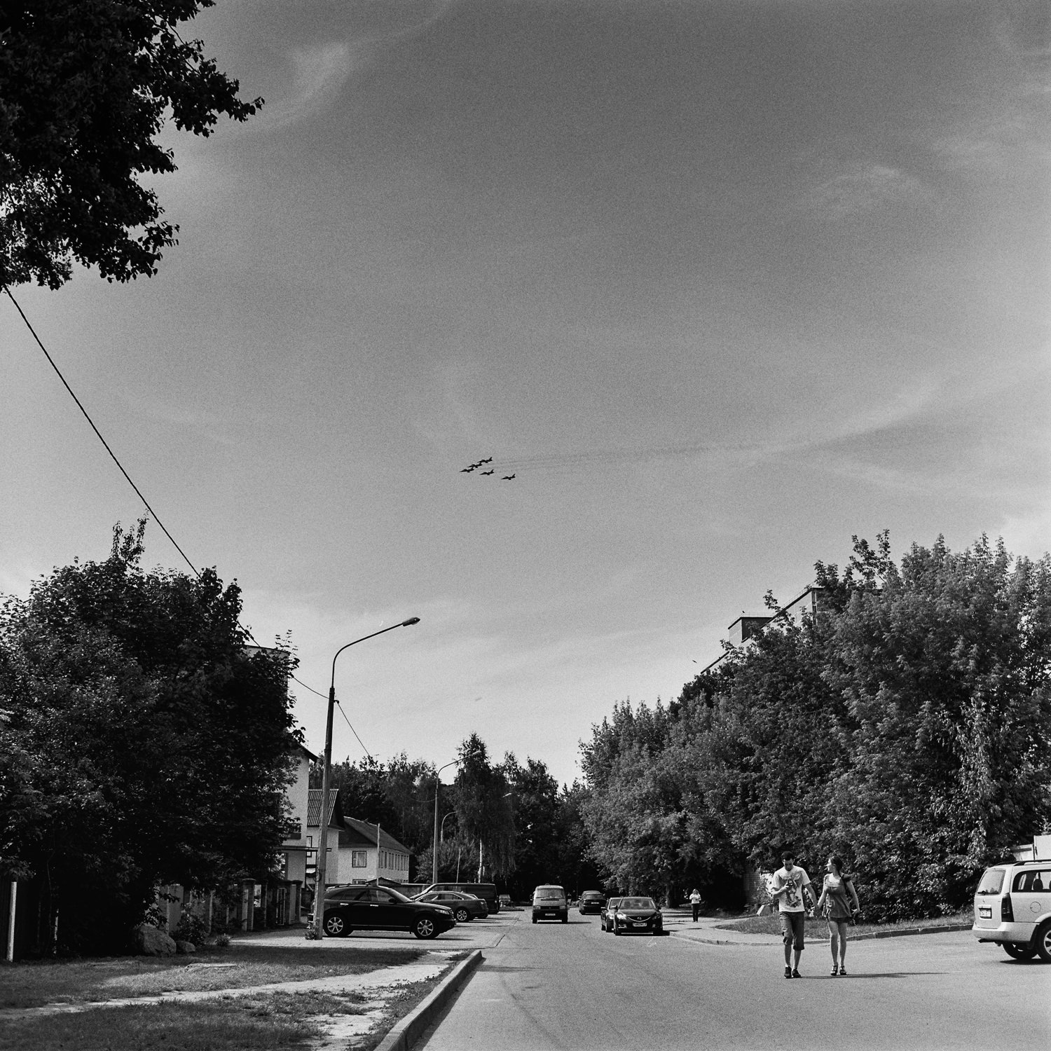 Boy and girl on the street watching five military planes flying over Minsk city