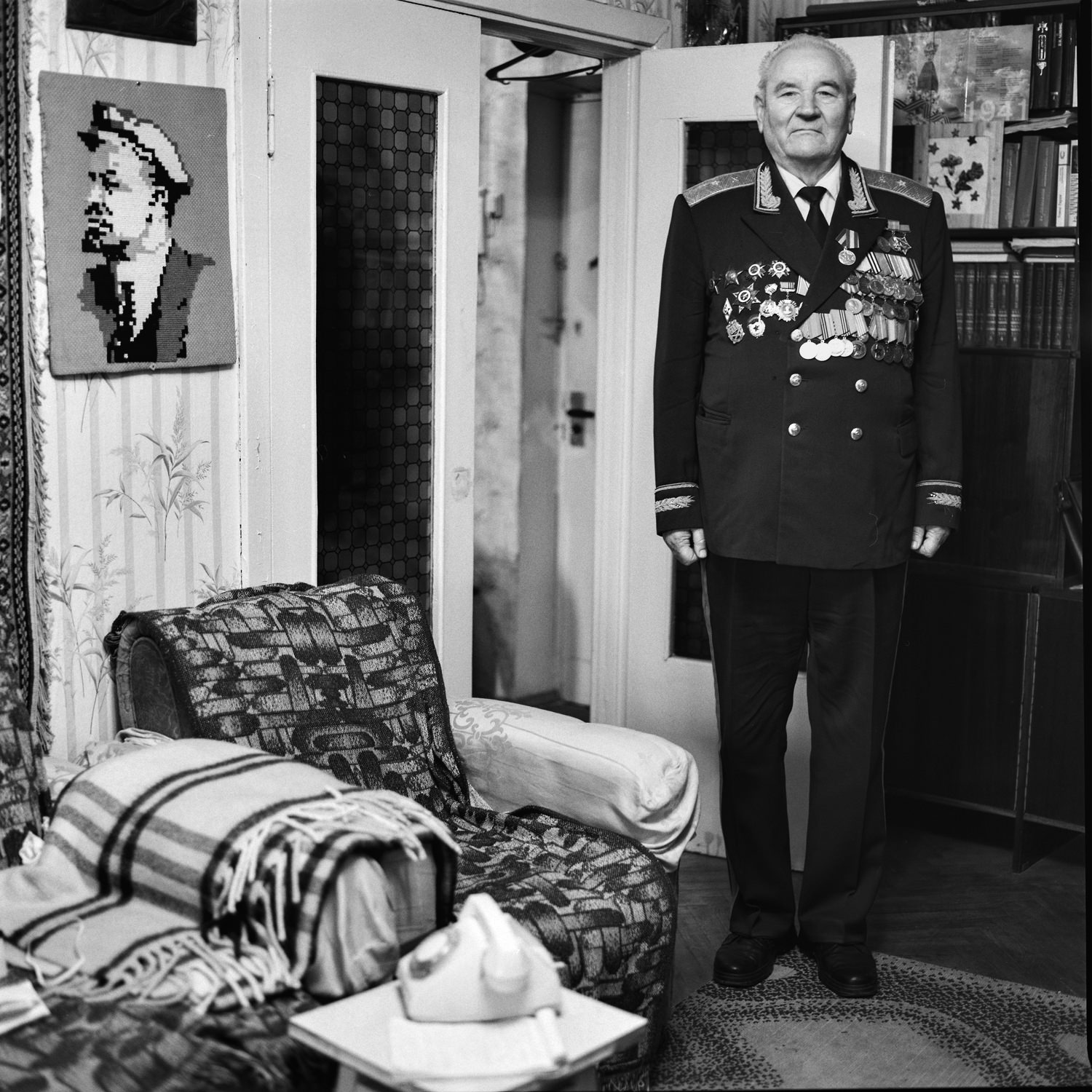 Portrait of the Great Patriotic War veteran in unifrm with medals standing still in his room with hand-made picture of Lenin on wall