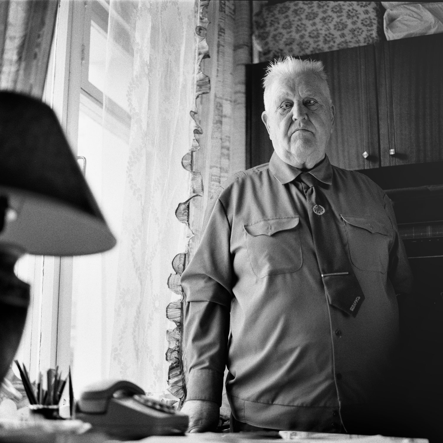 Black-and-white photo portrait of old Great Patriotic War survivor standing in his room behind the table with lamp and phone in Minsk, Belarus