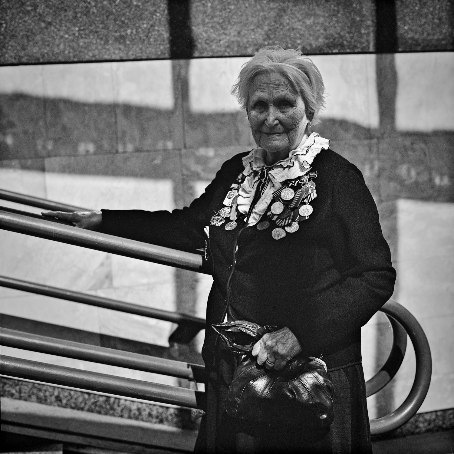 Portrait of elderly woman veteran of the Great Patriotic War standing in the underground passage taken on medium format camera and black-and-white film