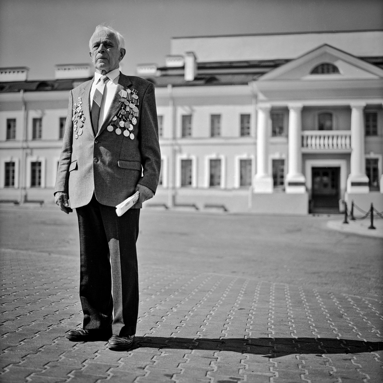 Black-white portrait of WW II veteran with medals standing in the center of Minsk city with newspaper in hand