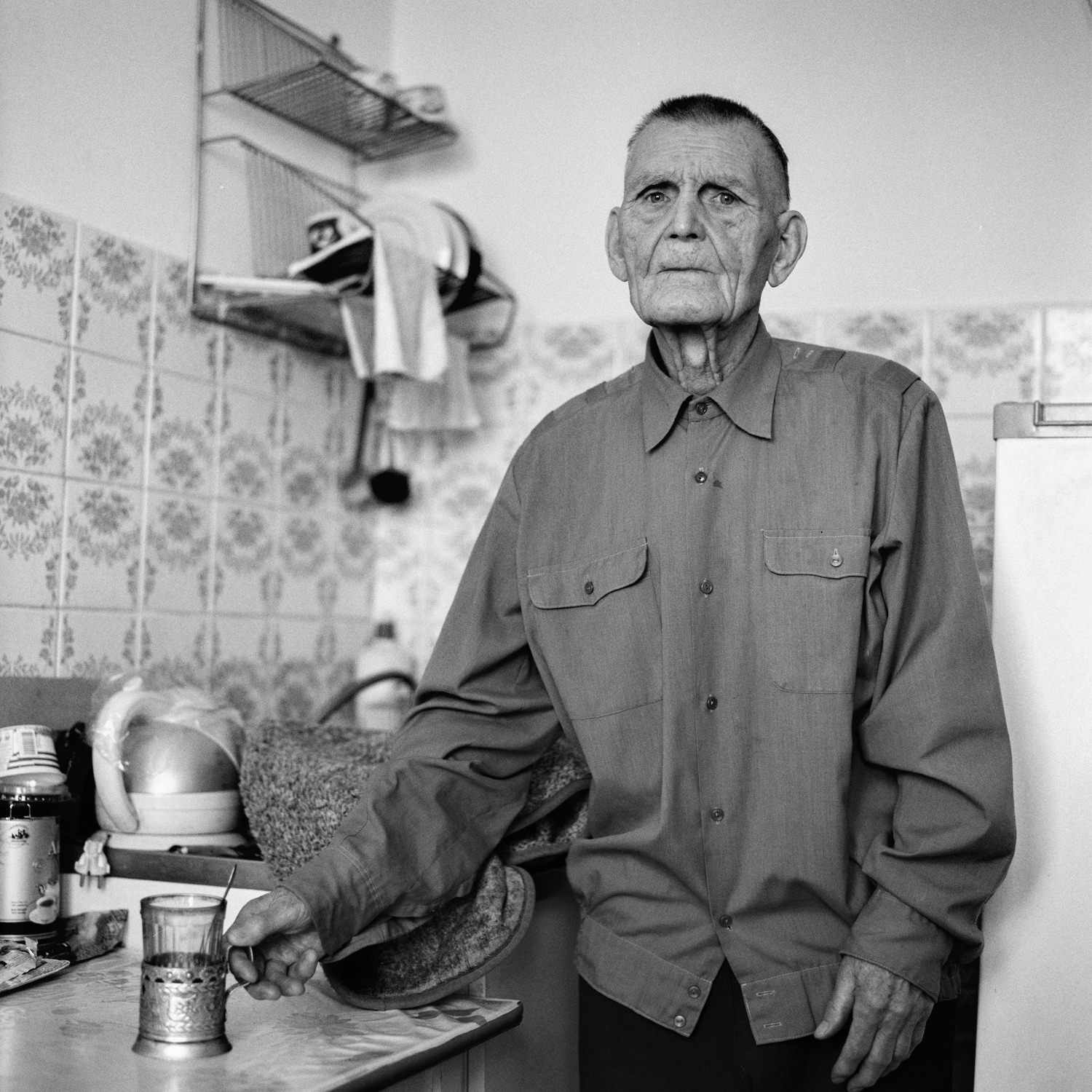 Captivating portrait of old prisoner of the concentration camp Auschwitz stands with a glass of tea in his hand in modest apartment in Minsk