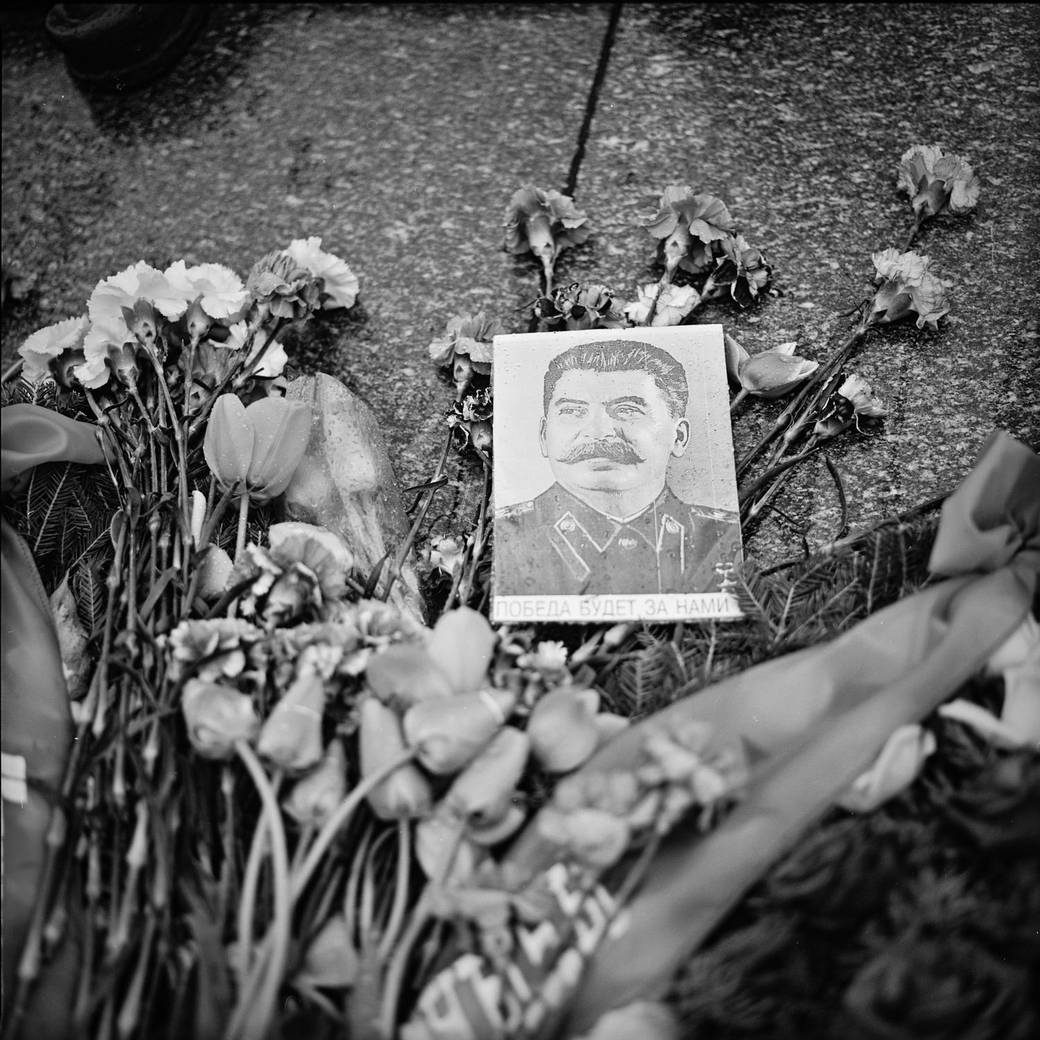 black-and-white photograph of Stalin and bouquets of flowers lie near the eternal flame in memory of victory over Nazi Germany