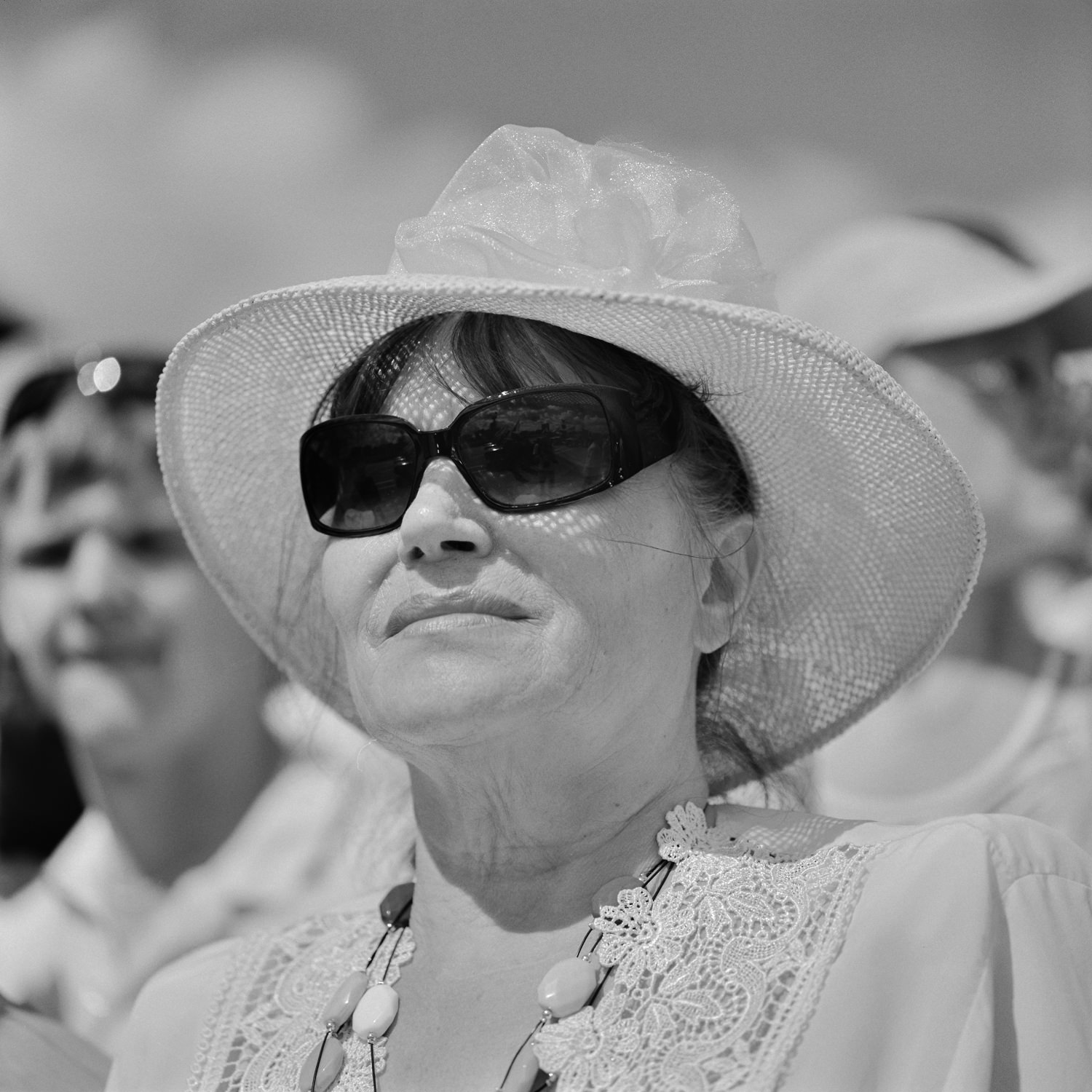 Close-up black-white portrait of stylish woman in a straw hat and black sunglasses watches the military parade of victory in Minsk