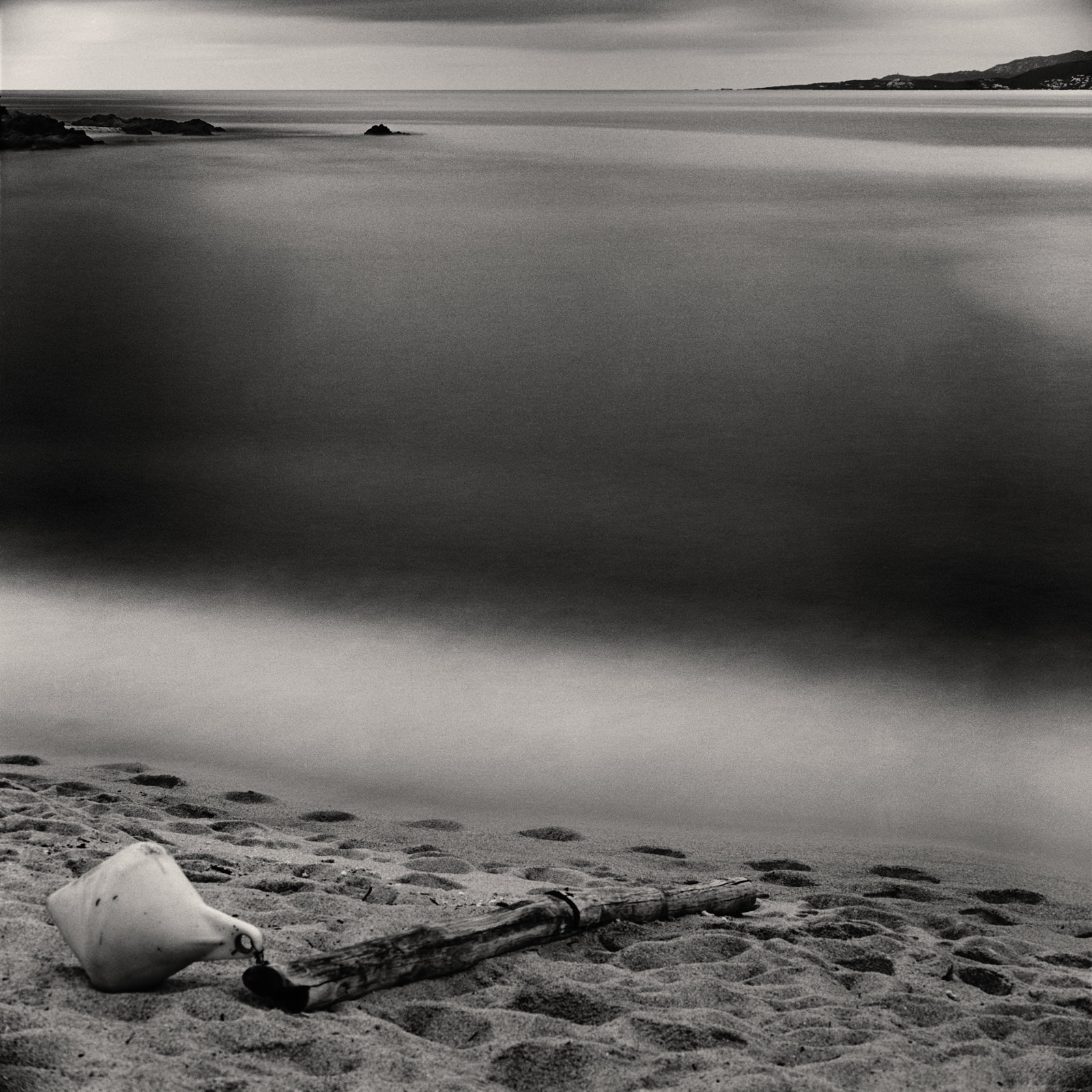 Long exposure waterscape photograph of Mediterranean sea with milky water, buoy and wooden stick on sand beach, made with medium format camera and black-white film, fine art print on paper