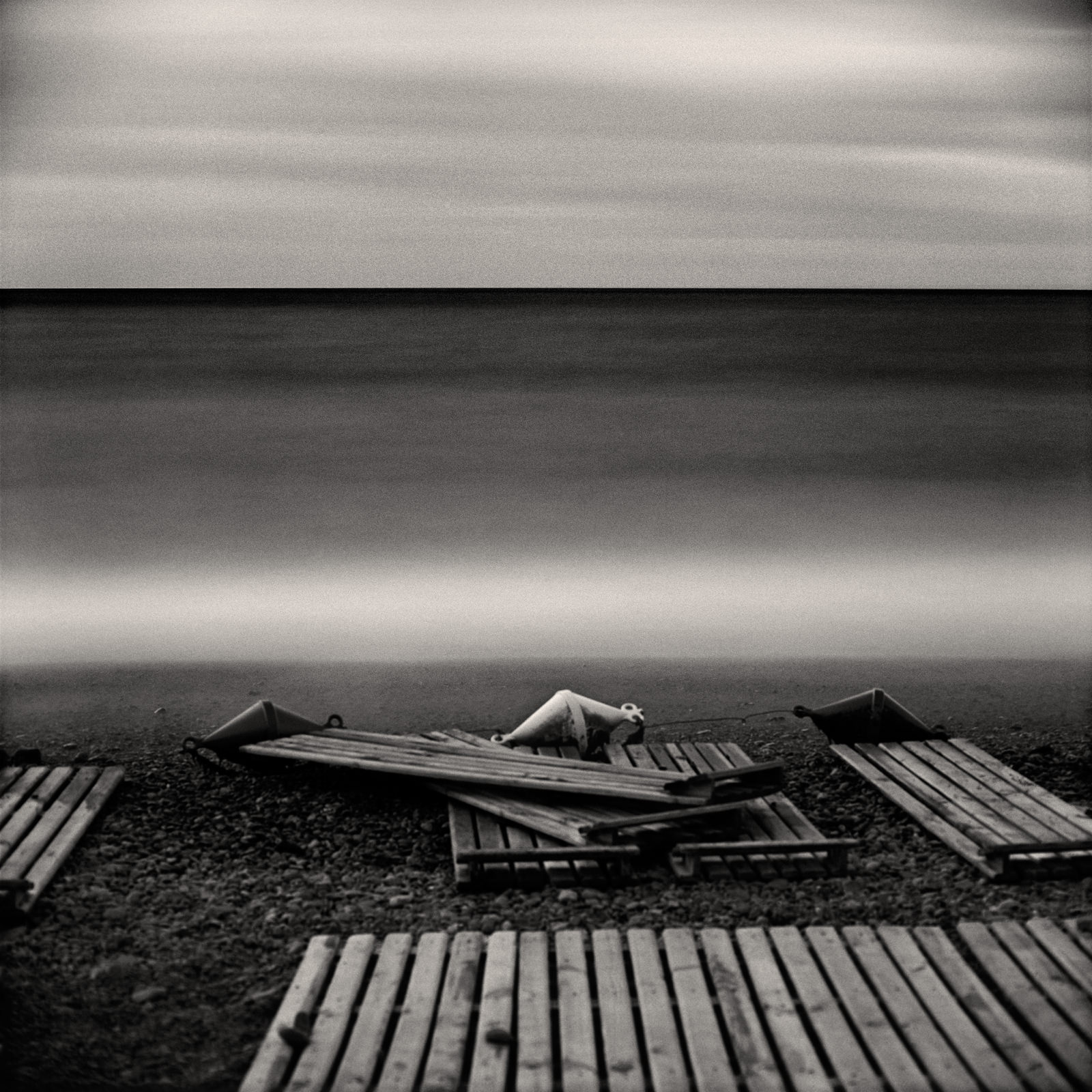 Nature photo long exposure seascape with silky sea waves and three buoys and beach loungers on the shore, made with black-white film and medium format camera Bronica Sq-Ai