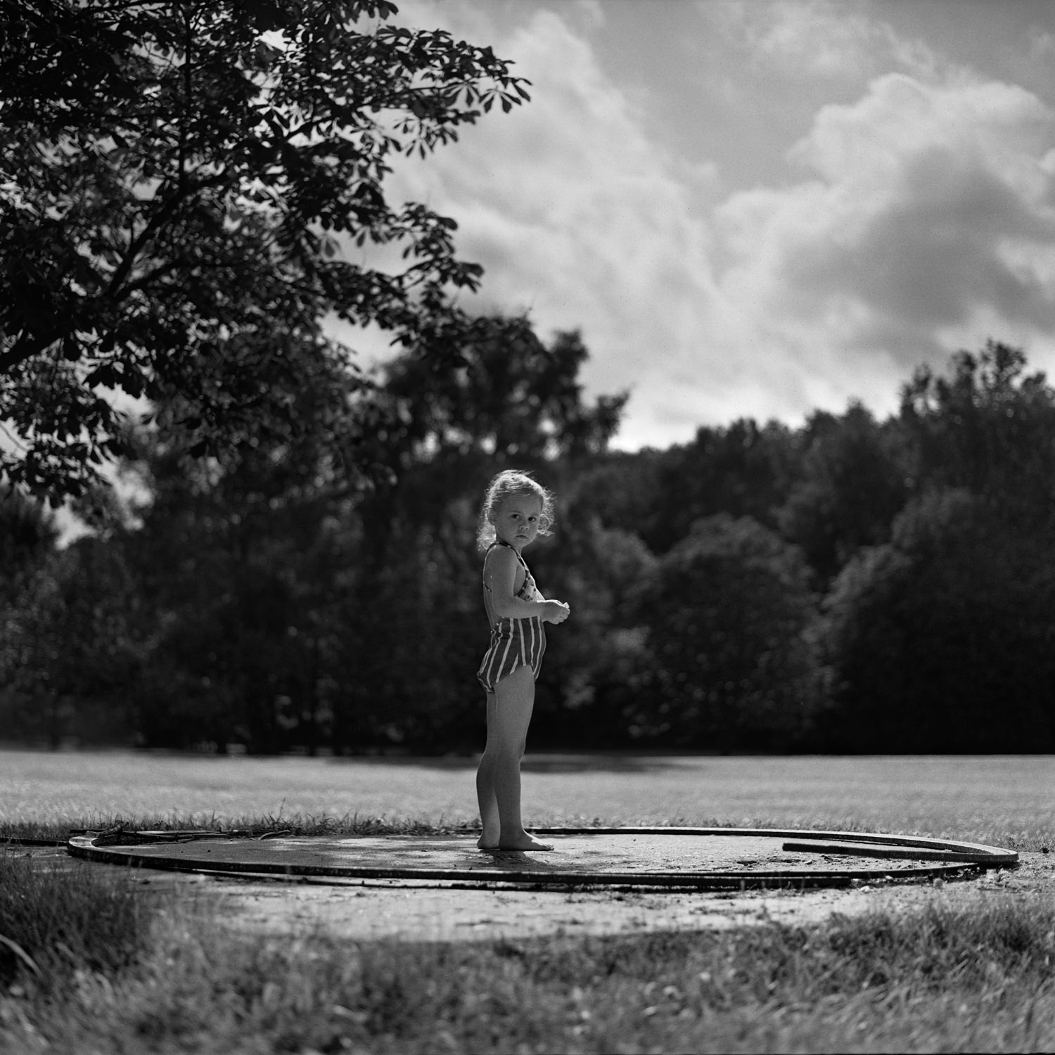 Fine art black white portrait of little girl standing in the circle under the tree