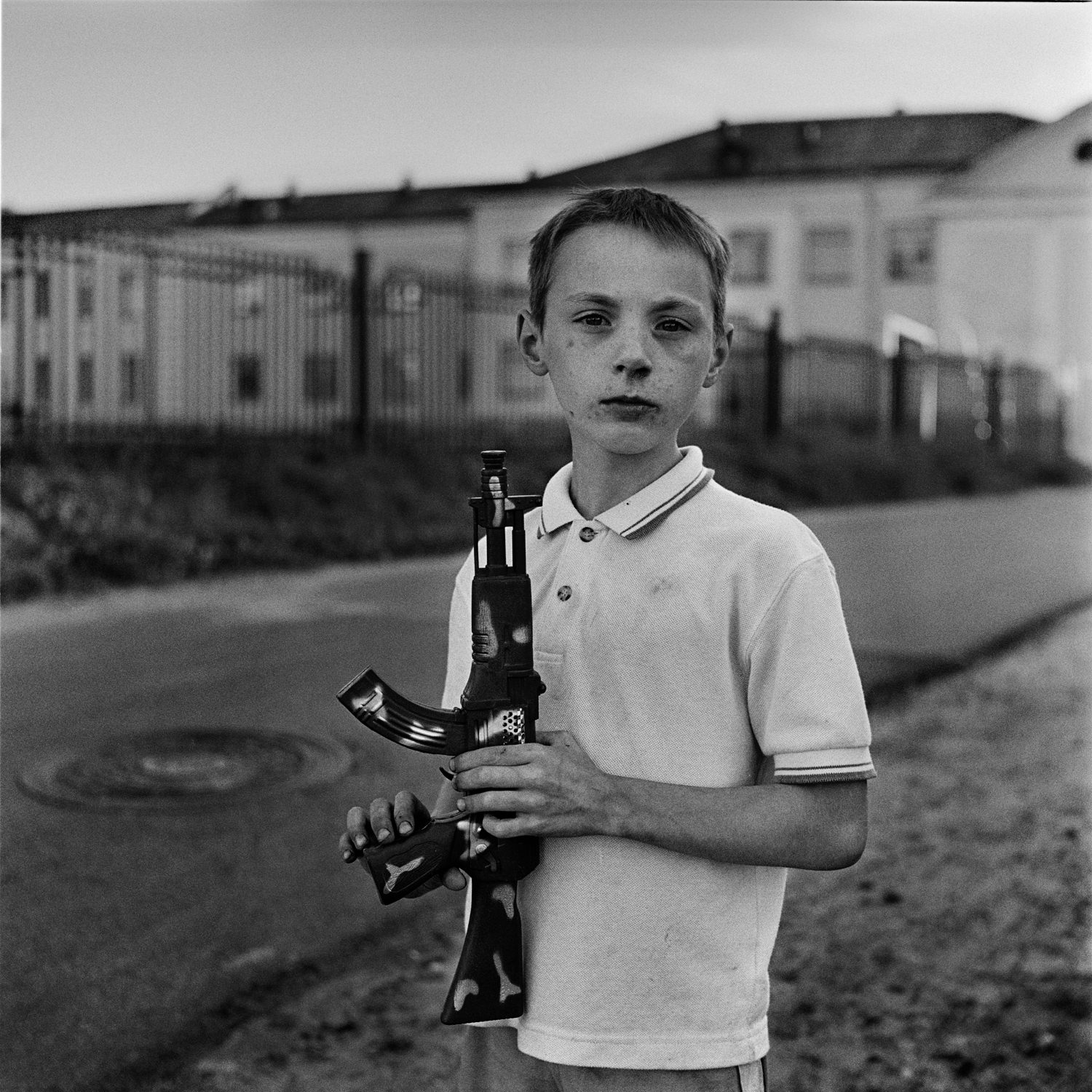 Dramatic black-white portrait of boy with dirty face handling toy machine gun in his hands with school building in background, Minsk city, Belarus
