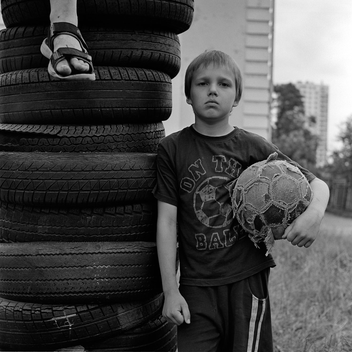 Black-white film portrait of a boy with a ball under his left hand and a friend sitting on a pile of car tires near school biulding in Mins city, Belarus