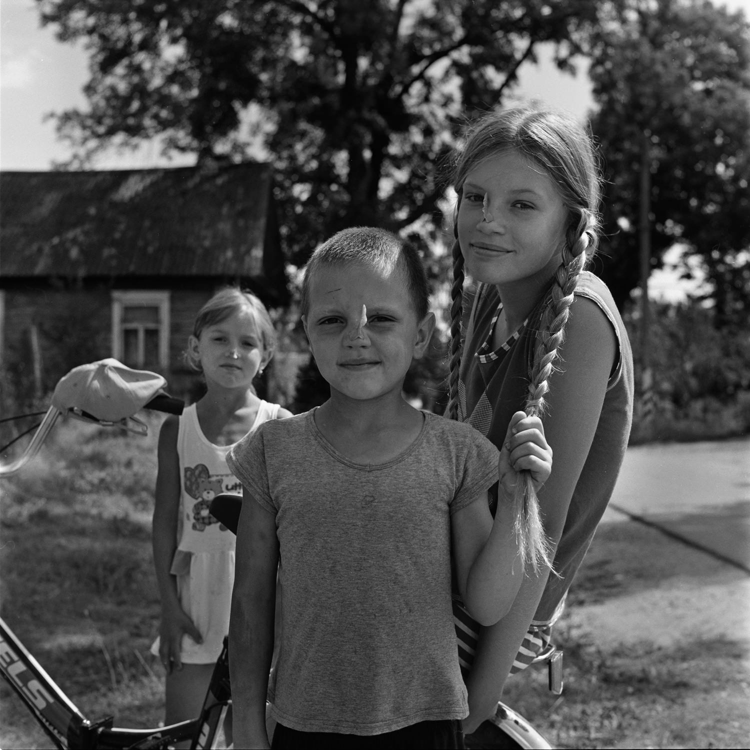 Group photo portrait of three children with maple seeds on their noses and a boy in the foreground holding the girl by her left pigtail