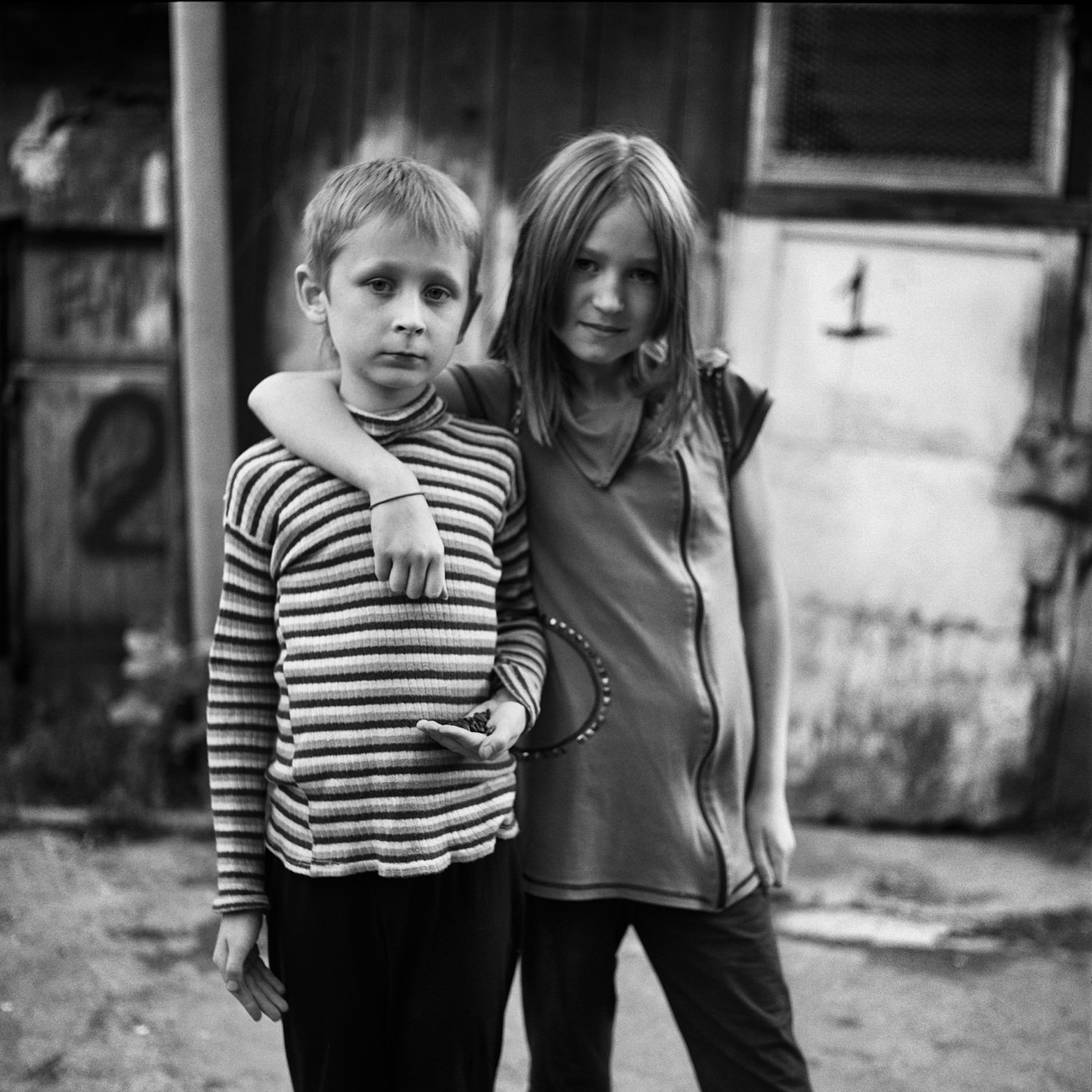 Portrait photo of two kids in suburbs of Minsk city - boy with sunflower seeds in his left hand and girl put her hand on the boy's shoulder