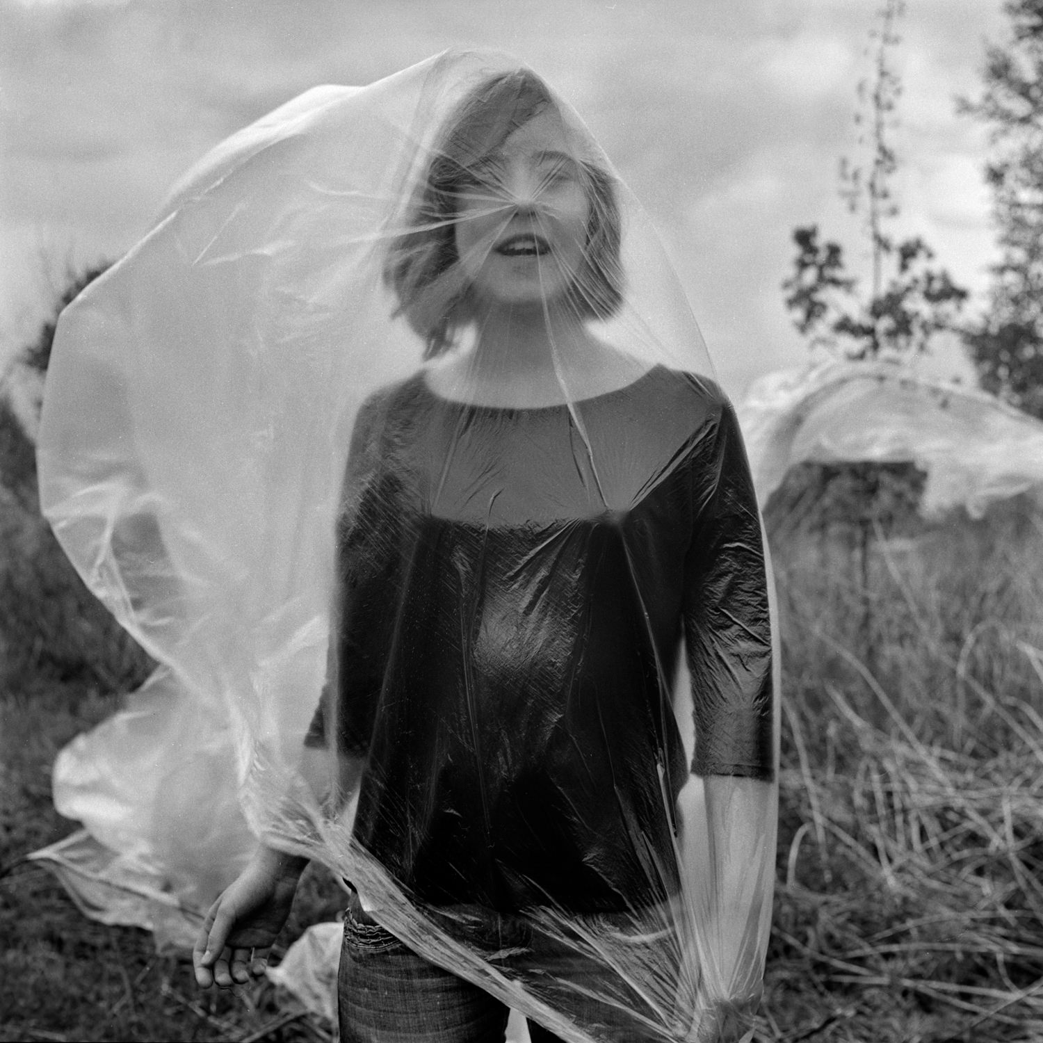 Emotional portrait of a laughing girl in the garden with a plastic bag flying out into the wind, covering the whole body