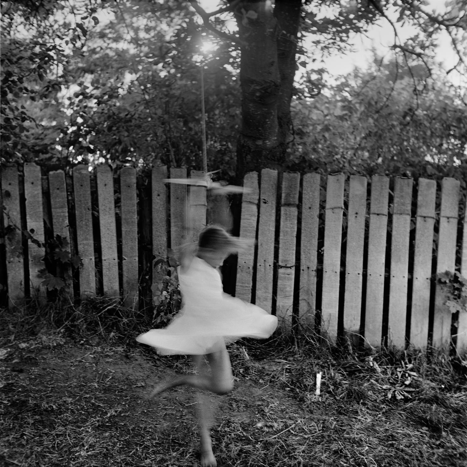 Black and white portrait of girl in light dress swirling on rope under an apple tree with fence in the background in the village, taken on film and medium format camera Yashica Mat 124G