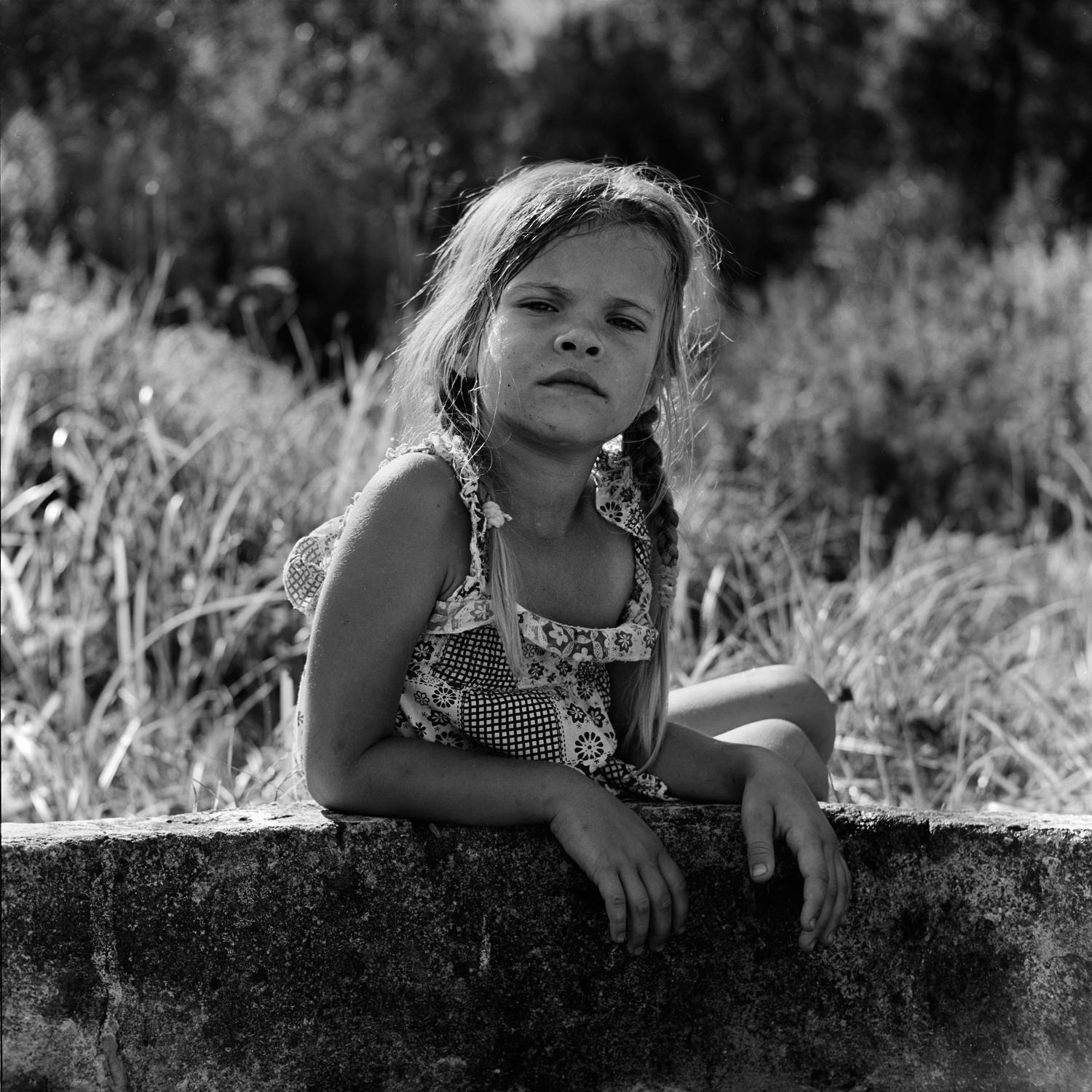 Expressive portrait of a little girl with pigtails and a light dress with her hands on a well with water on a hot summer day taken on black-white film