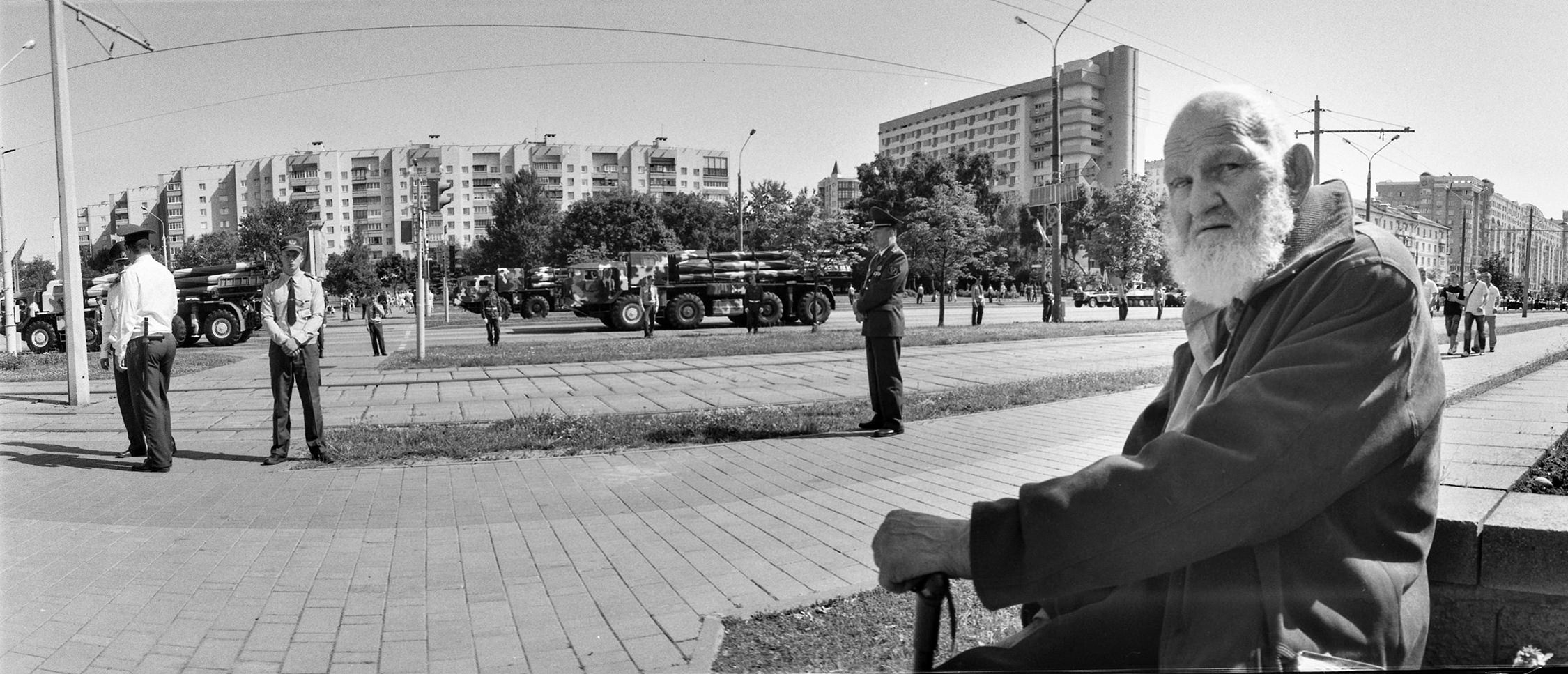 Black-white street portrait of an old veteran watching military parade with armored vehicles in the center of Minsk city, Belarus © Alexander Kladov