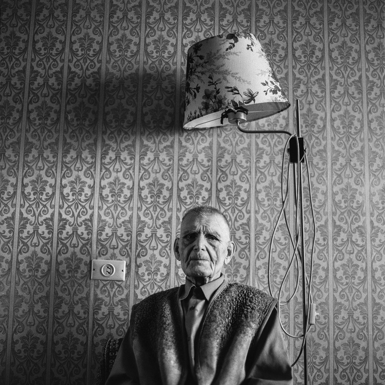 A lonely old soldier of Great Patriotic War sits in a chair under a floor lamp in warm clothes in his apartment