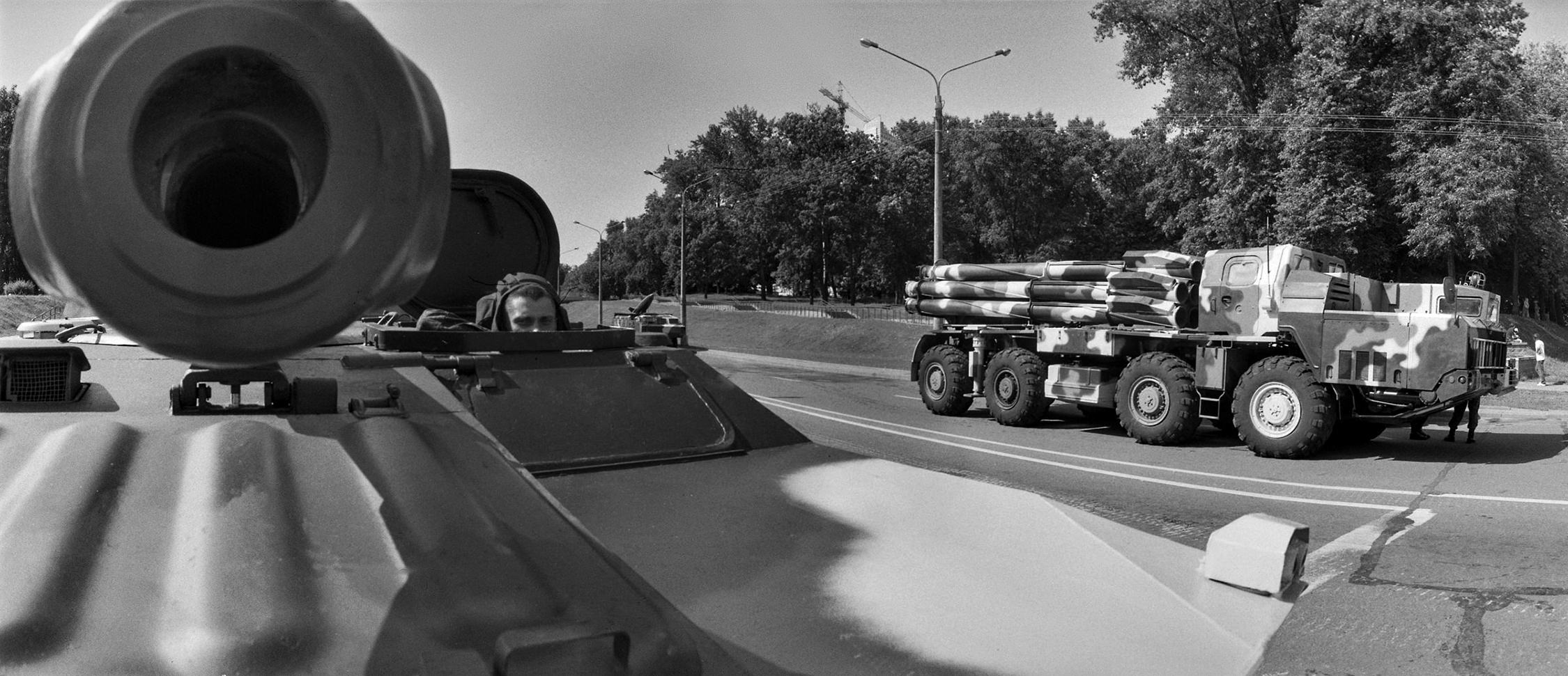 Black-and-white street photograph of tank driver protruding from the hatch of armed vehicle