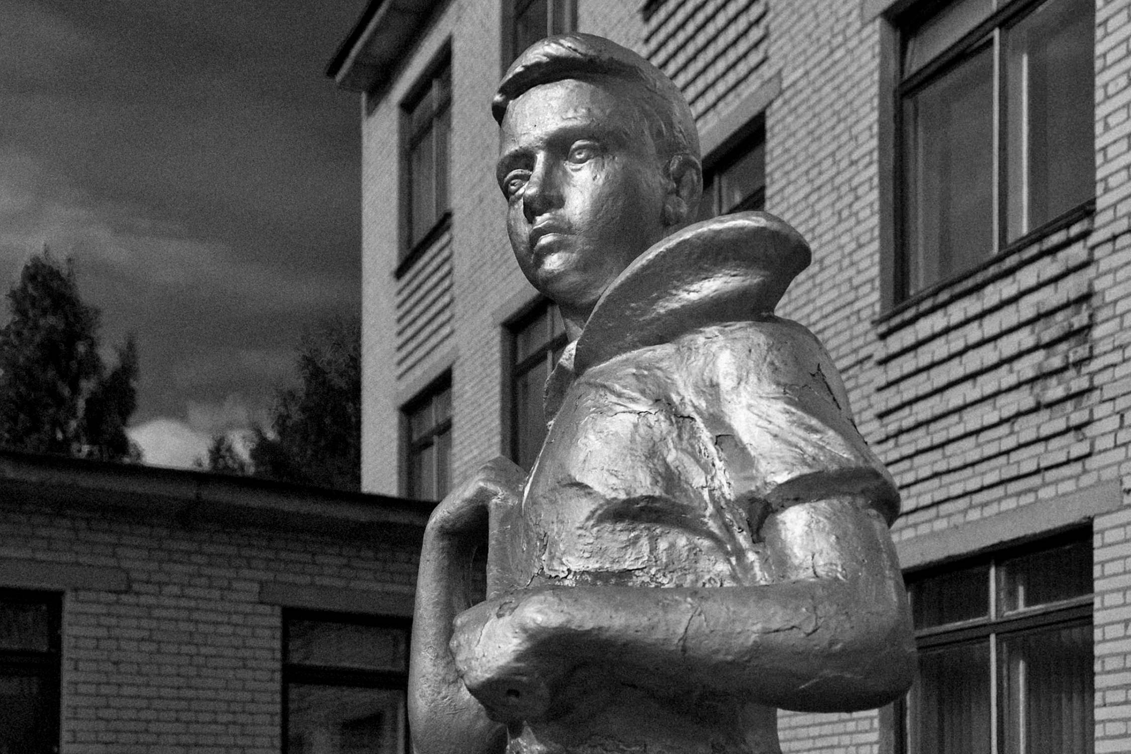 Cracked monument of USSR pioneer standing near secondary school