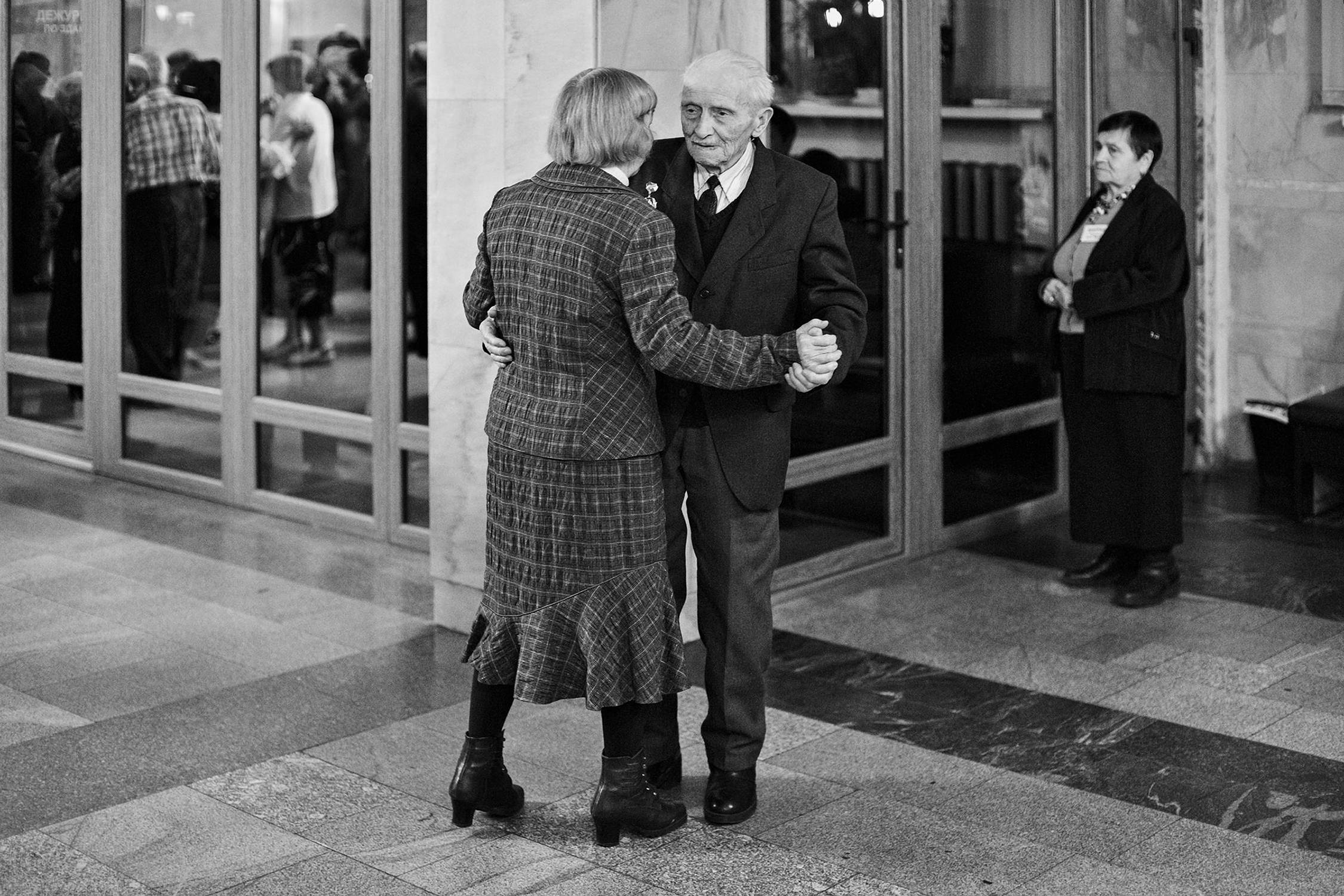 Reportage photo of old married couple dancing in the hall at veterans party in Minsk