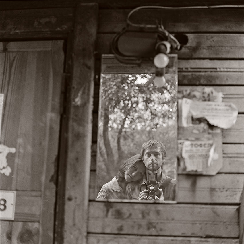 Alexander Kladov self portrait with his wife and medium format film camera Yashica Mat G124 as a reflection in old mirror hanging on the wall of wooden house in Minsk, Belarus